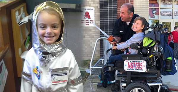 A smiling female student dresses as an astronaut and a male student in a wheelchair uses a fire hose with a firefighter