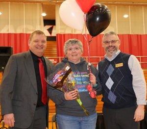 Mrs. Linda standing with two other adults receiving balloons and a bouquet of flowers