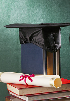Mortar board with a tassel and a diploma sit on top of stacked books
