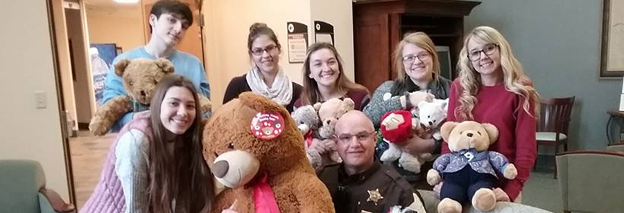 Students and a police officer pose with teddy bears