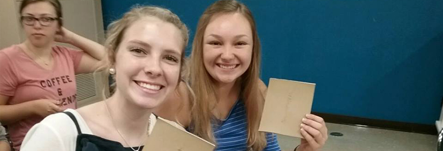 Two female students hold up their projects as they sit at their desks