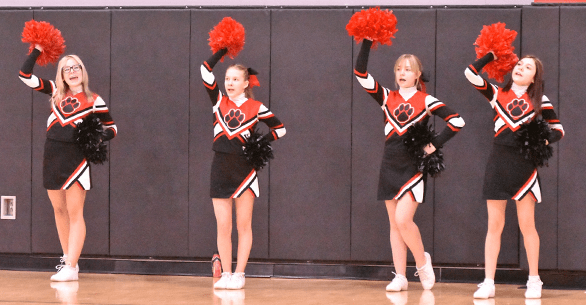 Four female cheerleaders cheering together