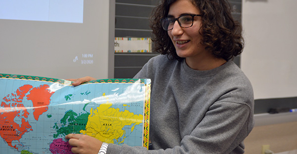 Teacher holding up a map in the classroom