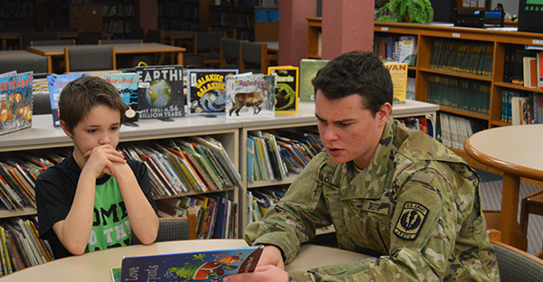 Young adult in Army fatigues reading a book with a younger male student