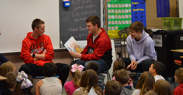 High school boys reading Cat in Hat book to younger students