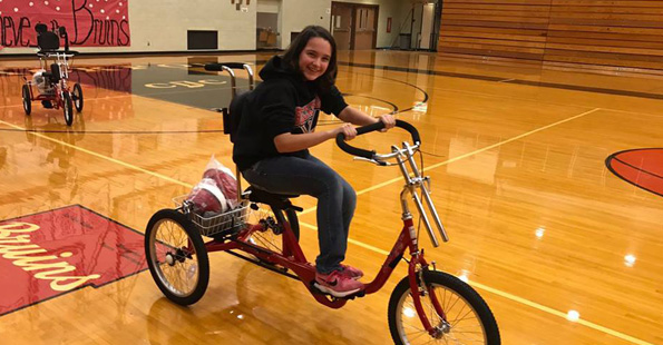 Woman on big tricycle in gymnasium