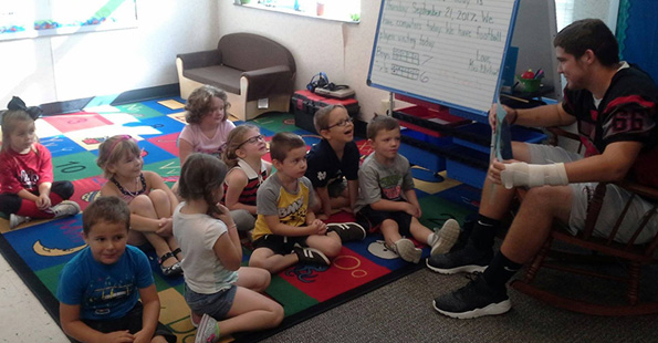 HS student reading to young children