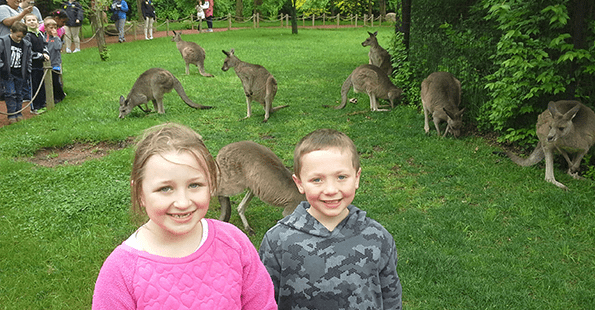 Two smiling students pose outside of a kangaroo zoo exhibit