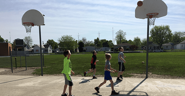 Students on a basketball court watch as a basketball goes into the net