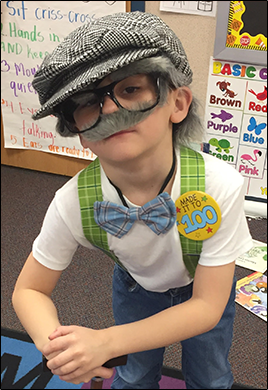 Male student dressed as an old man and wearing a button reading Made it to 100