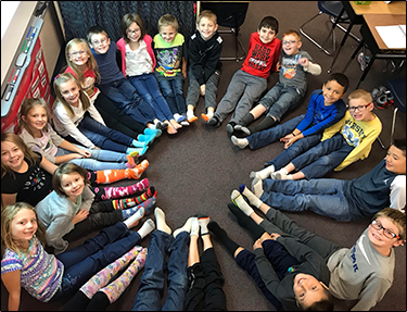 Students sit on a floor and form a circle with their feet