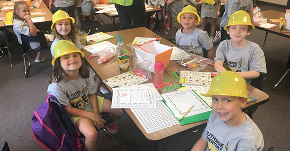 Students pose as they wear construction worker hats