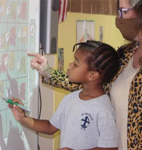 Teacher assisting student on SmartBoard