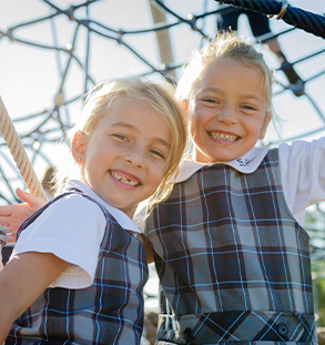 Two young female students on playground equipment