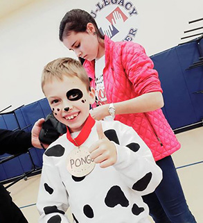 Smiling elementary school boy in a cow costume