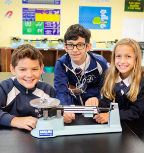 Two male students and female students weighing objects on scale