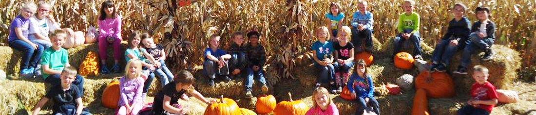 Students pose with pumpkins and hay