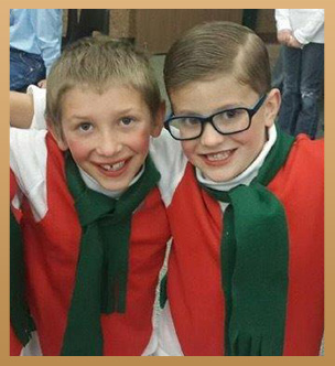 Two students wearing festive outfits pose together