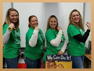 Staff members pose with We Can Do It Rosie the Riveter poster