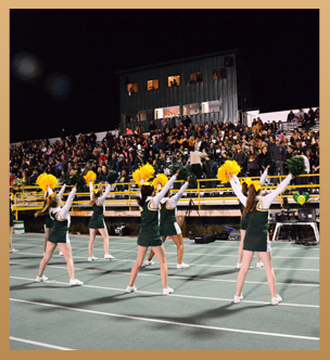 Cheerleaders cheer as a crowd watches on bleachers