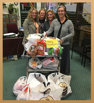 Staff members pose with bags of Thanksgiving food