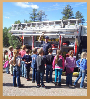Students stand near a fire engine