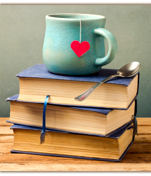 Cup with a heart shaped tea bag string and a spoon on top of stacked books