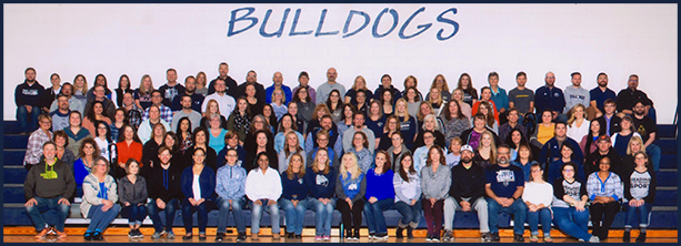 Administration and staff posing together on gym benches in front of text reading Bulldogs
