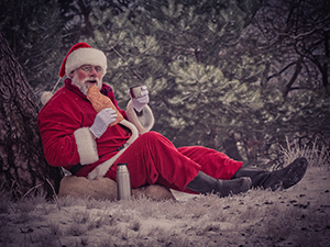 Santa eating while sitting under a tree