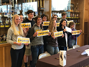Students hold up signs reading I'm University of Wyoming Bound