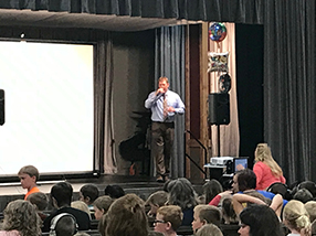Teacher stands on a stage with a microphone as he speaks to an audience