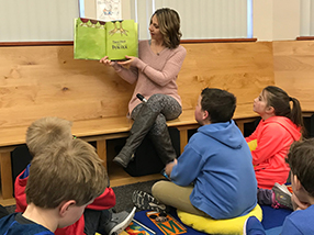 Teacher holds up book and reads to students