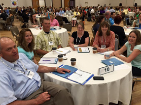 Teachers pose together at a round table