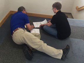 Teacher and student sit on the floor and work on class assignments