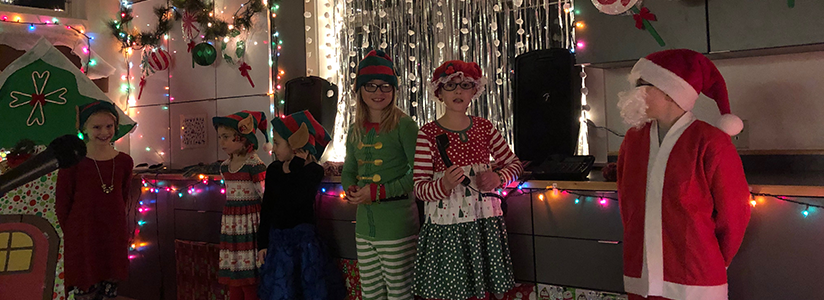 Students dressed in Christmas attire pose at a holiday event
