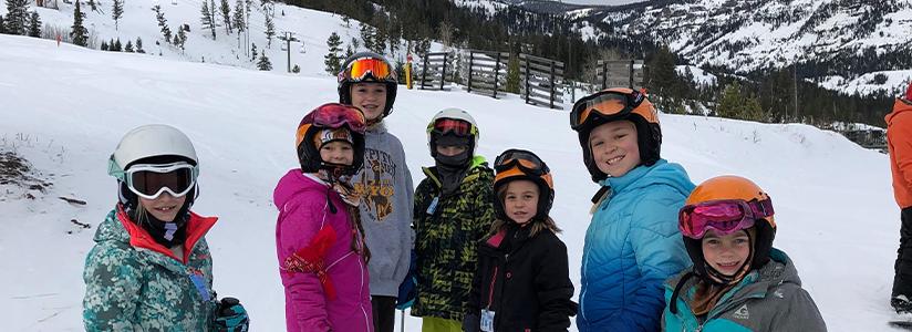 Students dressed in ski attire pose on ski slopes