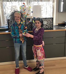 Two students dressed in costumes hold up a craft tree