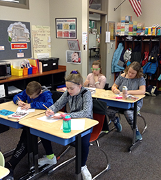 Students writing an assignment at their desks