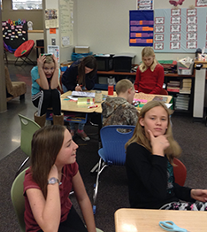 Students pulling funny faces while sitting at their desks