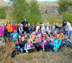 Students and teachers pose together on an outdoor field trip