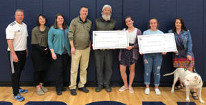 Adults and students standing with two large checks