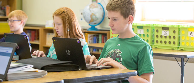 Three students use laptops in class