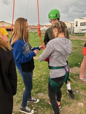 Students attaching harness for rock climbing