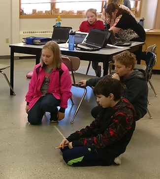 Students sit on the floor looking at a robot