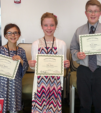 Three students holding up award certificates