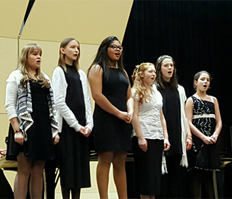 Six female students sing together on a stage