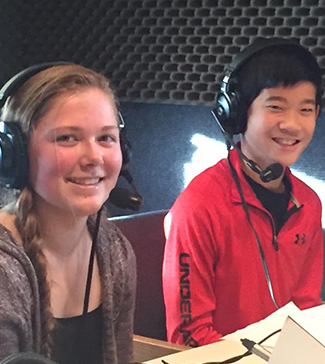 Two students wearing headphones smile
