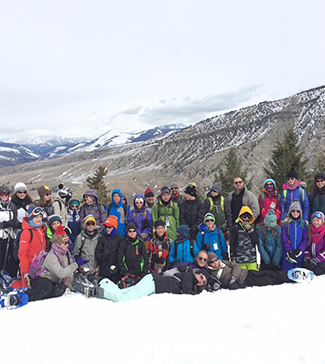 Students and teachers wearing ski attire pose on a snow covered mountain