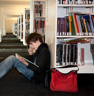 Male student sits on the floor of a library and reads