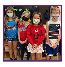 Four students posing in the classroom with masks